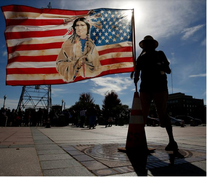 Jennell Downs, of the Kickapoo Tribe of Oklahoma, putting up a flag at the state capitol in Oklahoma City during a protest of the Dakota Access pipeline last month. Steve Gooch/The Oklahoman, via Associated Press