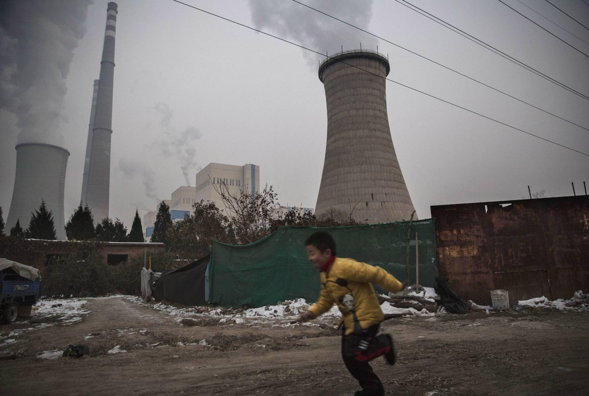 Um menino corre perto de uma central térmica de carvão em Pequim (China).  KEVIN FRAYER GETTY IMAGES / EPV